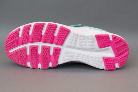 one sports shoe with a red white sole on a gray background. Bottom view  Stock Photo
