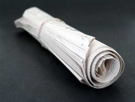 Rolled up newspaper with rubber band on black background