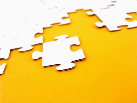 ingenuity: White puzzle pieces isolated on yellow background