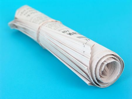 rolled up newspaper isolated on blue background Stock Photo