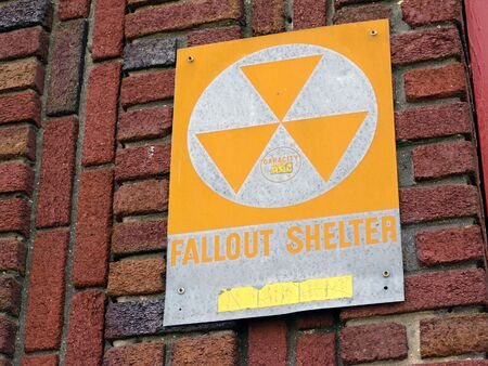 vintage fallout shelter sign attached to brick wall photo
