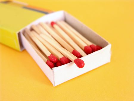small box of red tipped wooden matches on yellow background