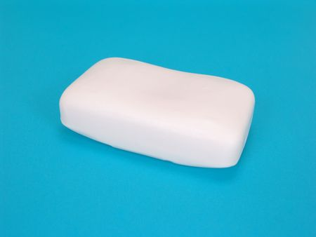 new bar of soap isolated on blue background