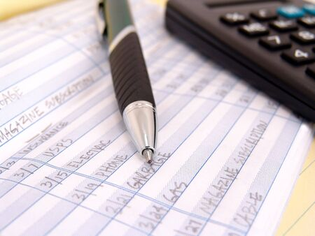 check book ledger with pen on yellow legal pad