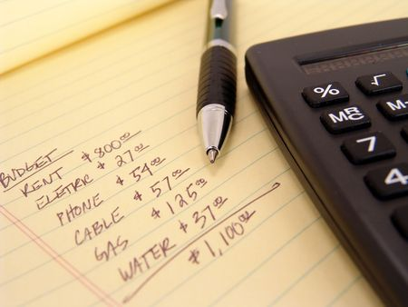 yellow legal pad with calculator and pen with budget written on pad