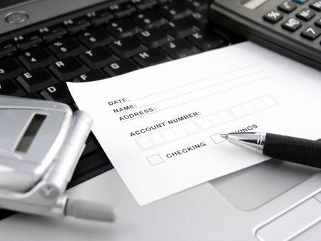 deposit slip: bank slip on keyboard with phone, pen and calculator