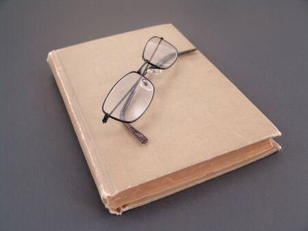 black rimmed: pair of black rimmed glasses on antique book