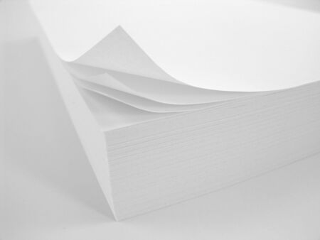 stack of white copy paper with curled corner over white background