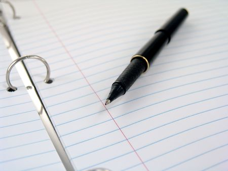close up of clasps in 3-ring binder with pen