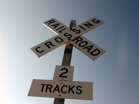 railroad crossing sign isolated against blue sky photo