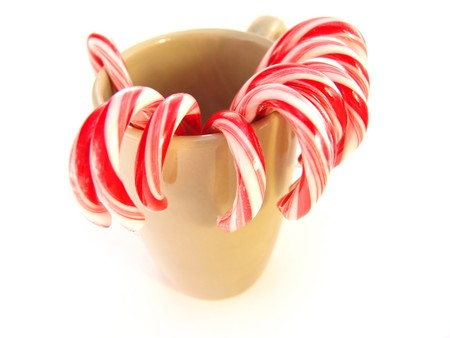 minty: red and white candy canes in green mug over white background
