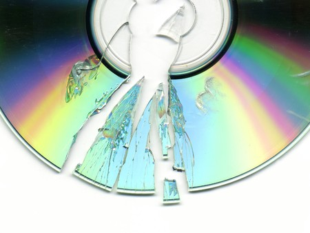 fragments: broken and cracked CD  DVD on white background