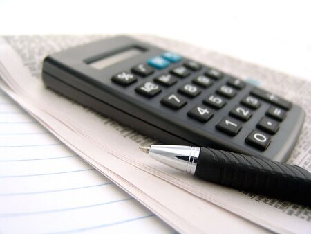 calculator with newspaper and pen over lined paper