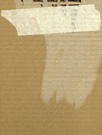 torn cardboard with masking tape on surface Stock Photo