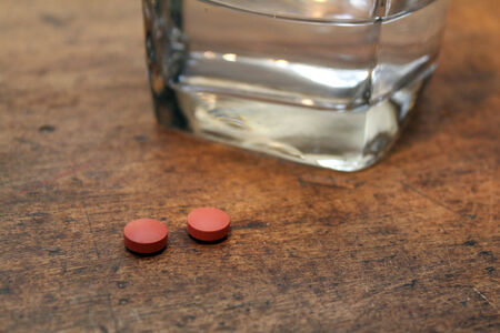 two loose pills over wood background with glass of water
