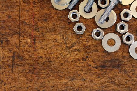 tornillos y tuercas: Tuercas, pernos y arandelas sobre el fondo de madera
