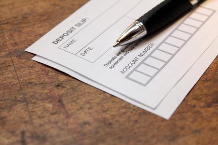 Papier Einzahlungsschein und Stift über Holz Hintergrund