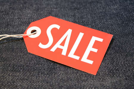 Sale tag with string on cotton denim  Stock fotó
