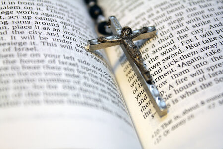 bible open: Black bead rosary in spine of open bible