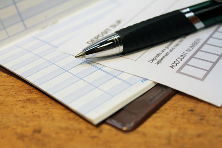 deposit slip: Paper deposit slip and pen with check ledger over wood background Stock Photo
