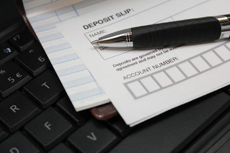 deposit slip: Deposit slip with pen and check book register on keyboard Stock Photo