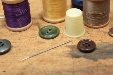 notions: Sewing notions, buttons needle and thread on rustic wood background