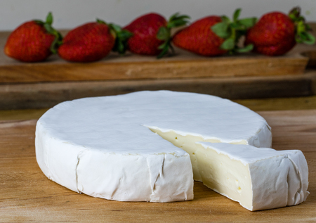 Round of camembert brie cheese with strawberries on the background