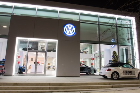 Vancouver BC, Canada - January 9, 2018: Office of official dealer Volkswagen. Volkswagen is a German automobile manufacturer specializing in high-performance and economy cars. Night shot all is illuminated.