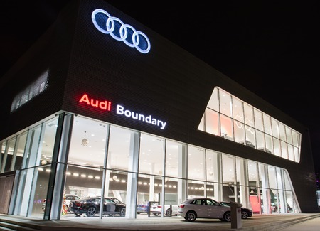 Vancouver BC, Canada - January 9, 2018: Office of official dealer Audi. Audi is a German automobile manufacturer specializing in high-performance and luxury cars. Night shot all is illuminated.