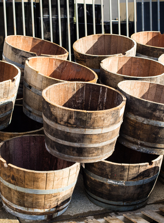 Stacked old wooden half barrels at gerden store is about to have second life as a flower planters or garden decoration.