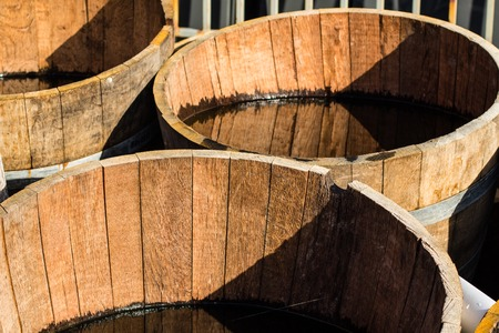 Old wooden half barrels. Ex wine casks having a second life to be used as decoration or as a flower planters.