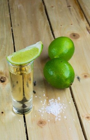 Mexican Gold Tequila with lime and salt on wooden table. Copyspace for text. Reklamní fotografie