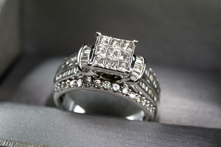 A diamond engagement ring in a box with glintreflection. Shimmering princess-cut diamonds. 스톡 콘텐츠