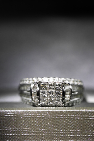 A diamond engagement ring in a box with glintreflection. Shimmering princess-cut diamonds. Imagens