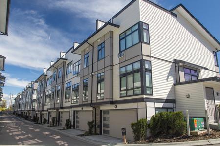 Beau développement de nouvelles maisons de ville. Façade extérieure d'une rangée de maisons urbaines modernes et colorées. Maisons neuves juste après la construction sur le marché immobilier