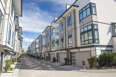 Nice development of new townhouses. External facade of a row of colorful modern urban townhouses.brand new houses just after construction on real estate market