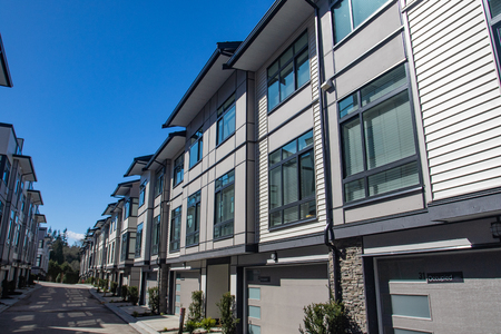 Brand new townhouse complex. Rows of townhomes side by side. External facade of a row of colorful modern urban townhouses. brand new houses just after construction on real estate market
