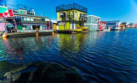 Floating Home Village colorful Houseboats Water Taxi Fishermans Wharf Reflection Inner Harbor, Victoria British Columbia Canada Pacific Northwest. Area has floating homes, piers, restaurants. Redakční