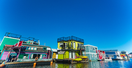 Floating Home Village colorful Houseboats Water Taxi Fisherman's Wharf Reflection Inner Harbor, Victoria British Columbia Canada Pacific Northwest. Area has floating homes, piers, restaurants. Editorial