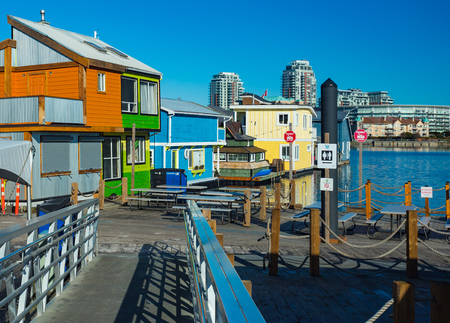 Floating Home Village colorful Houseboats Water Taxi Fisherman's Wharf Reflection Inner Harbor, Victoria British Columbia Canada Pacific Northwest. Area has floating homes, piers, restaurants. 免版税图像
