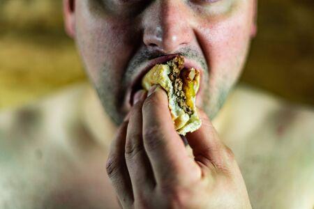 Man eating Burger. Topless man eating burger. Standard-Bild