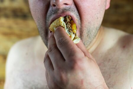 Man eating Burger. Topless man eating burger. Standard-Bild - 138722020
