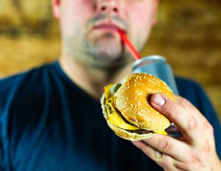 Man with burger and can of pop drink.