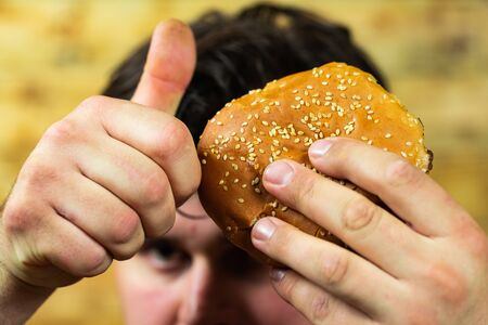 Young man eats delicious appetizing burger. 免版税图像