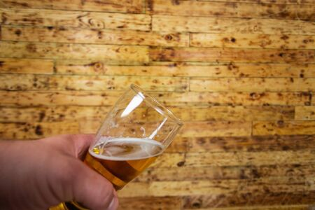 Mans hand holding glass of beer. Wood background. 免版税图像