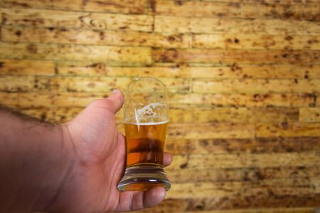 Mans hand holding glass of beer. Wood background. Standard-Bild