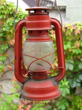 red oil lamp: an old oil lamp on a coming red woodbine background