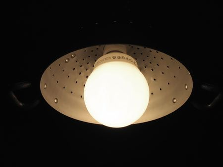 fluorescent lamp mounted in an aluminiun pasta colander (clipping path) photo