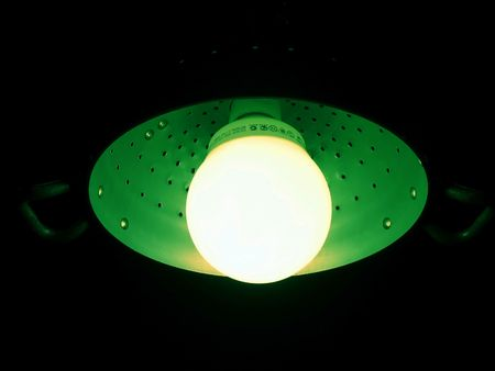 green fluorescent lamp mounted in an aluminium pasta colander (clipping path) photo