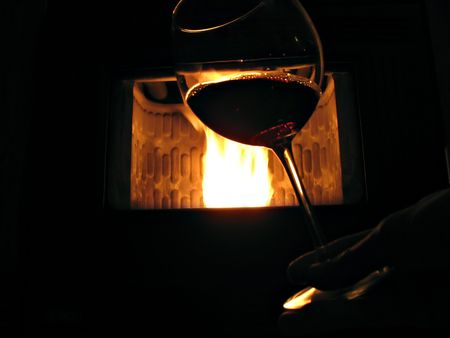 Taste a glass of red wine in front of the fireplace photo